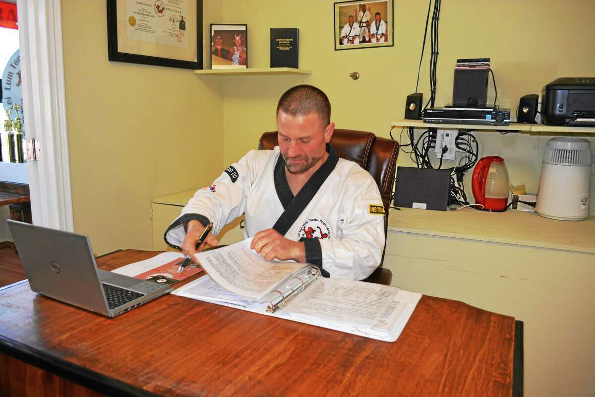 Frank Sinicrope, fourth-degree black belt and owner of Western Karate Federation, works from his desk at his studio on 191 Main St. in Middletown.