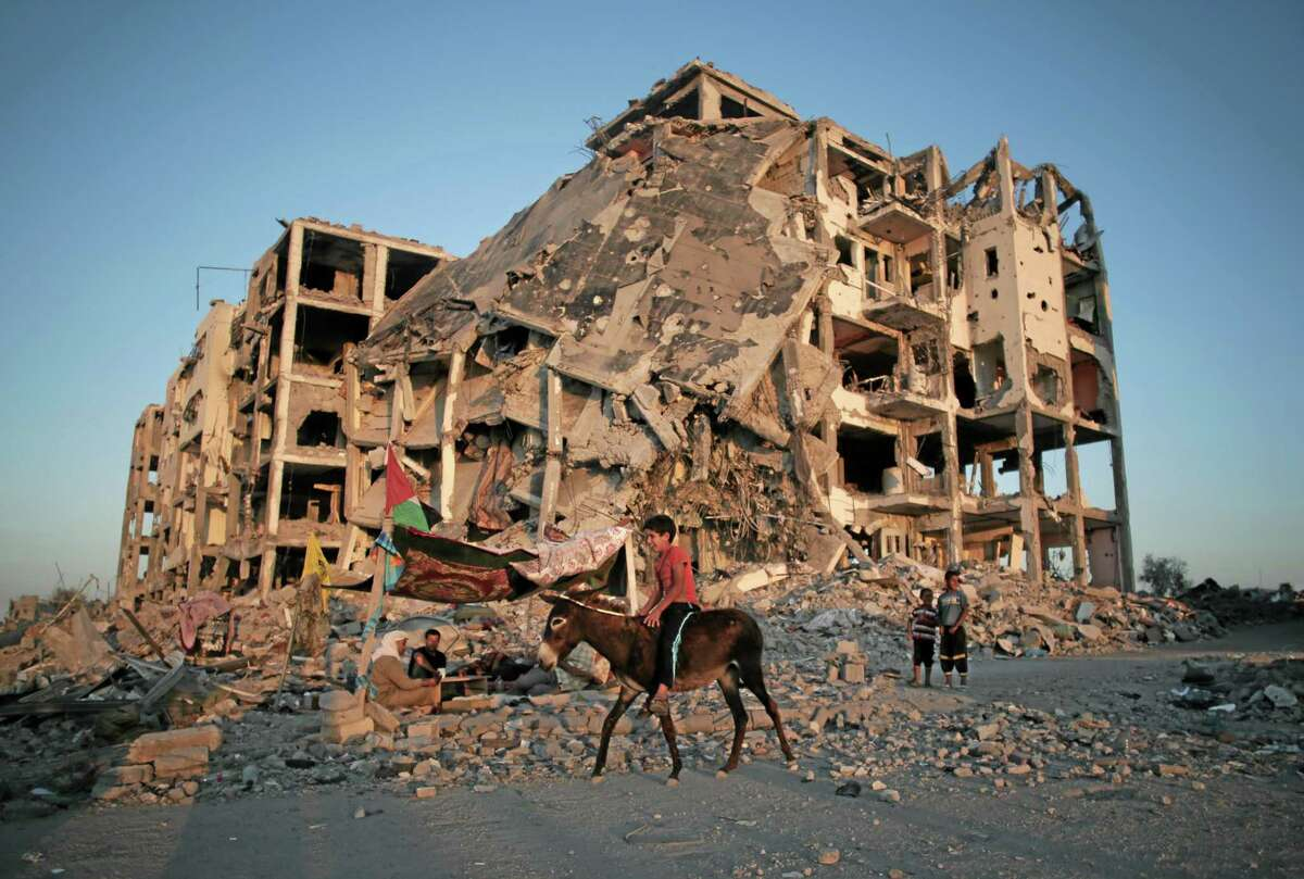 A Palestinian boy rides a donkey next to the destroyed Nada Towers residential neighborhood in the town of Beit Lahiya, northern Gaza Strip, Monday, Aug. 11, 2014. (AP Photo/Khalil Hamra)