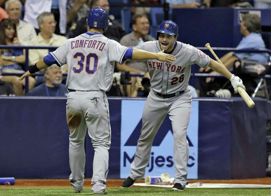 New York Mets rookie Michael Conforto celebrates with Daniel Murphy after scoring on an RBI single by Wilmer Flores in the ninth inning of Friday night's 4-3 win over the Tampa Bay Rays in St. Petersburg, Fla. Photo: Chris O'Meara — The Associated Press  / AP