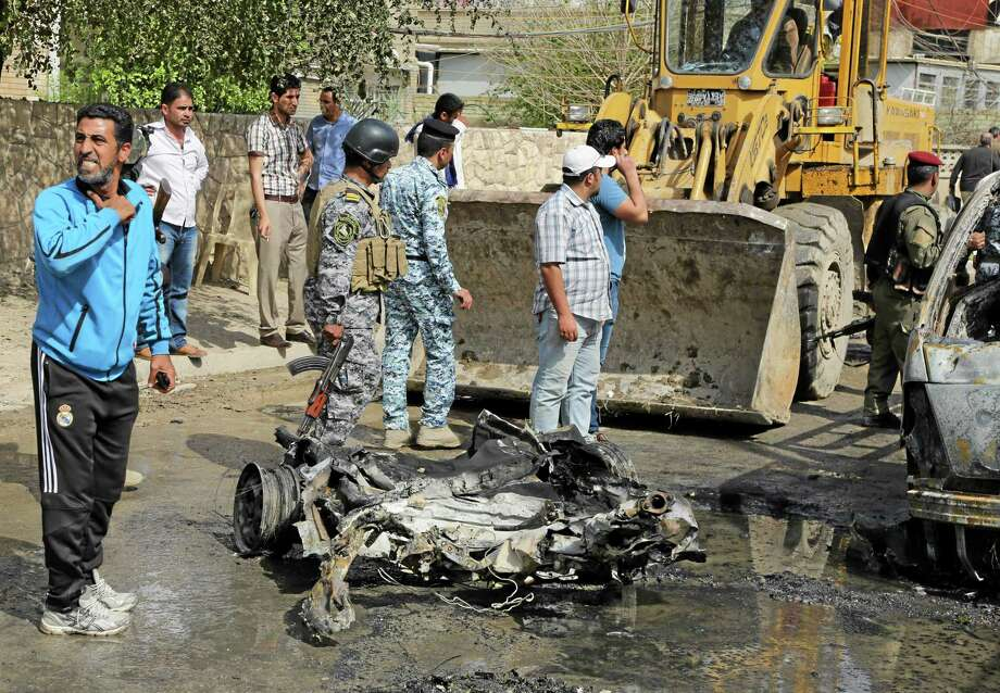 A municipality bulldozer cleans up while Iraqi security forces and others gather at the site of a car bomb attack in Baghdad, Iraq, Wednesday, March 5, 2014. A series of car bombs hit Wednesday in commercial areas of Baghdad, that killed and wounded scores of people, according to Iraqi officials. (AP Photo/Karim Kadim) Photo: AP / AP