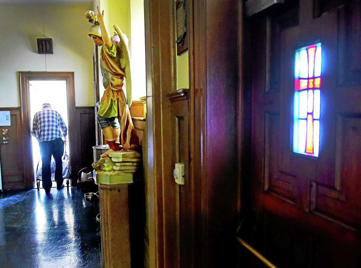 Edwin Norse, owner of Saint Joseph's Statue Repair of Middletown, 68, walks from the church sanctuary to his workshop in the rectory of the church where he pushes through his own pain to restore life to objects that are dying.