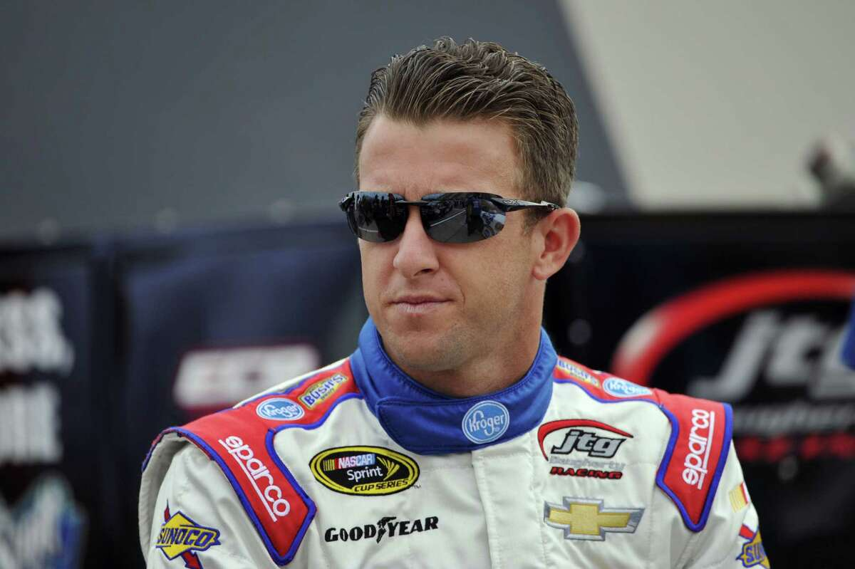 AJ Allmendinger waits by his car Saturday before qualifying first for the NASCAR Sprint Cup race at Watkins Glen International in Watkins Glen. N.Y.