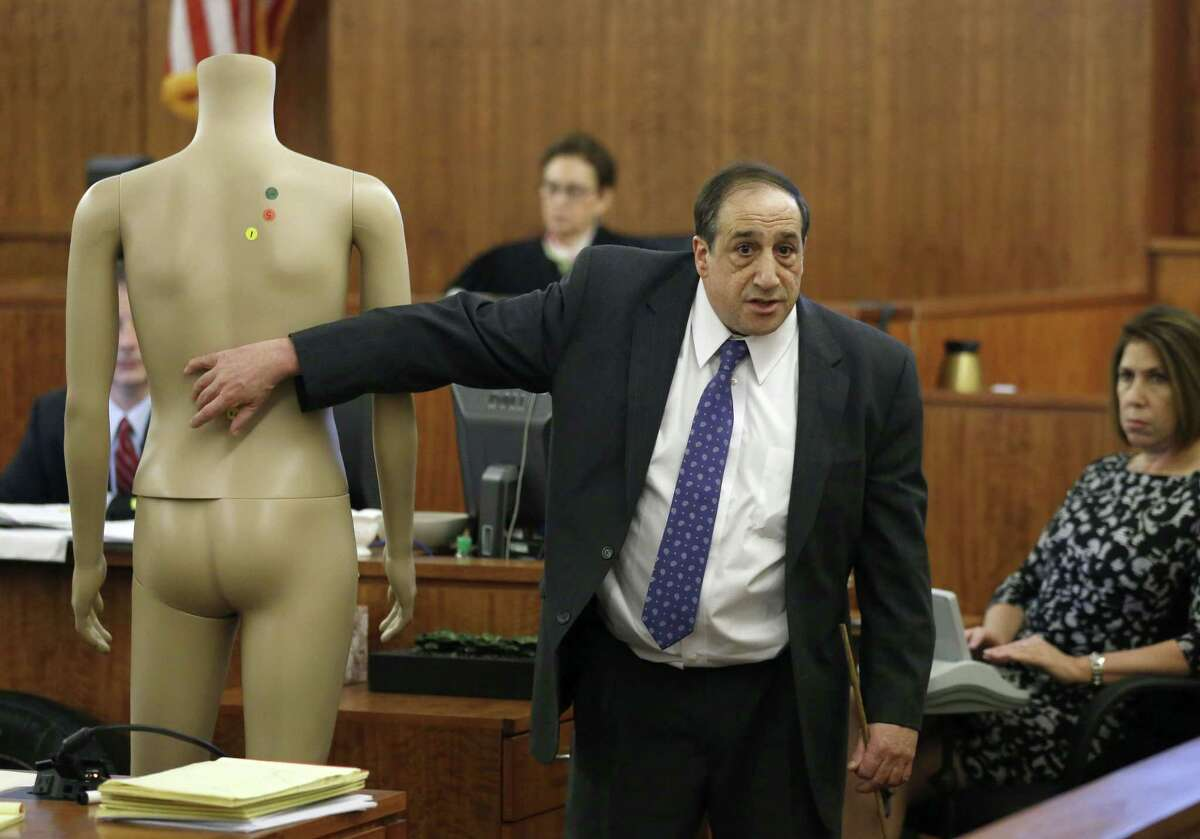 William Zane, of the Massachusetts state medical examiner's office, points to a mannequin while testifying about the location of bullet wounds in the body of Odin Lloyd during the murder trial of Aaron Hernandez on Thursday in Fall River, Mass.
