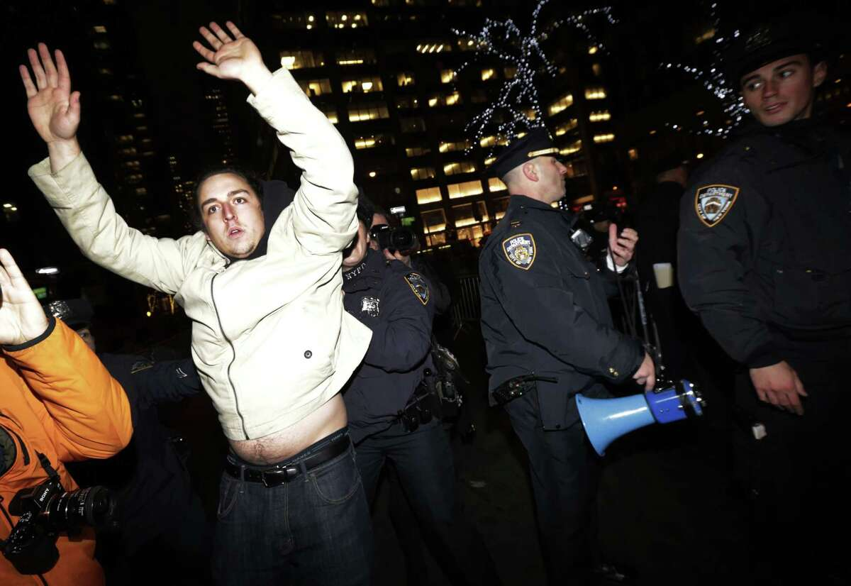 A man, left, holds his hands up as New York City Police officers secure a street near Rockefeller Center during a protest after it was announced that the police officer involved in the death of Eric Garner is not being indicted, Wednesday, Dec. 3, 2014, in New York.