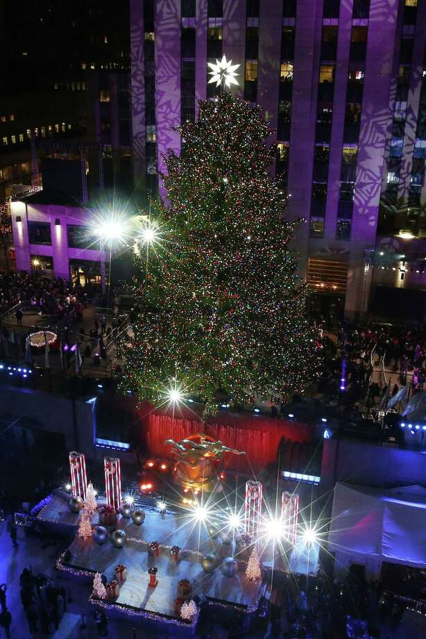 The Rockefeller Center Christmas tree is lit following a ceremony in New York on Wednesday, Dec. 3, 2014. Weighing approximately 13 tons, the 85-foot tall, 90-year-old Norway Spruce is adorned with 45,000 energy efficient LED lights. (AP Photo/Jason DeCrow) Photo: AP / FR103966 AP