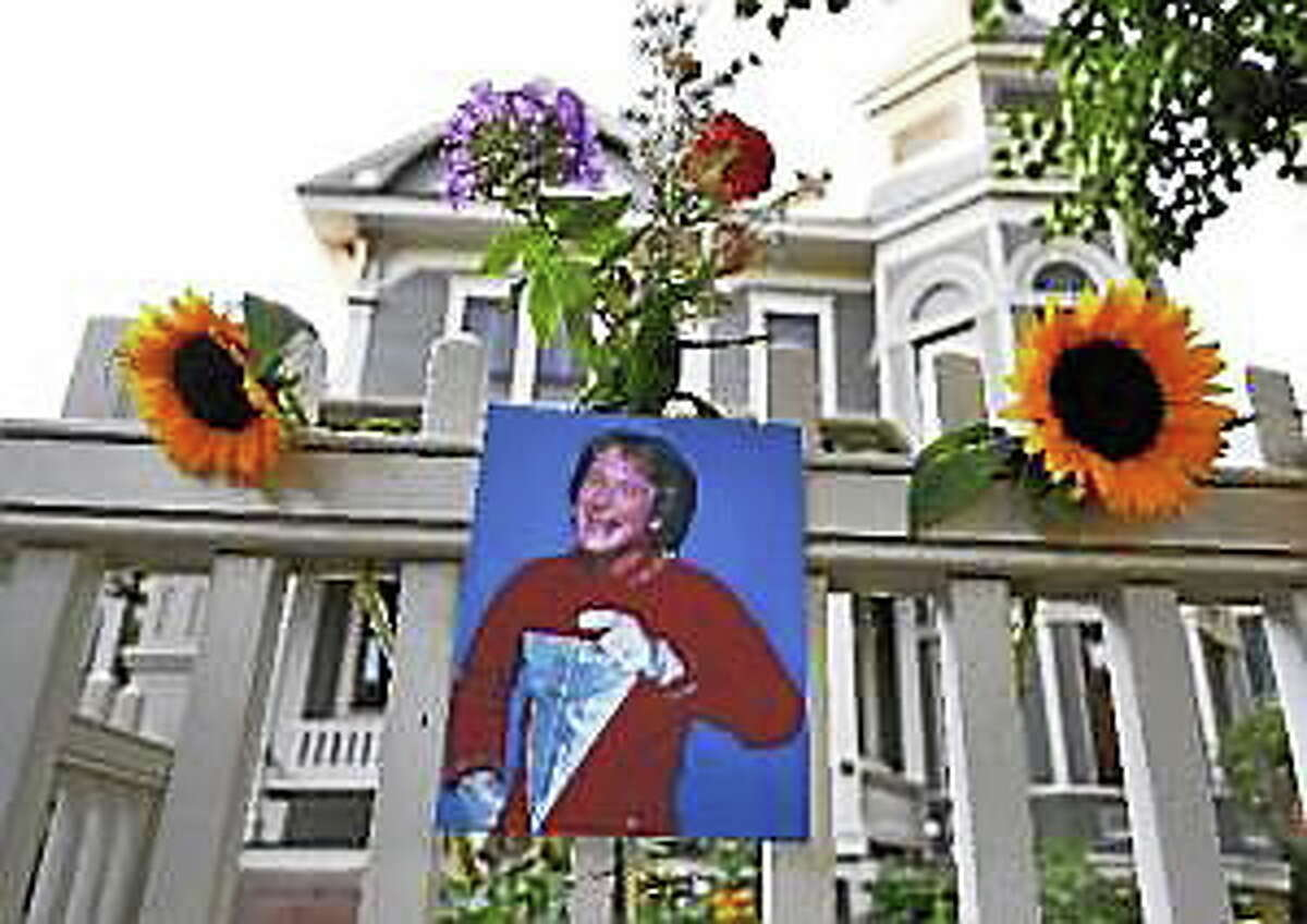 """A photo of the late actor Robin Williams as Mork from Ork hangs with flowers left by people paying their respects, in Boulder, Colo., Monday Aug. 11, 2014, at the home where his hit 80's TV series """"Mork & Mindy"""", was set."""