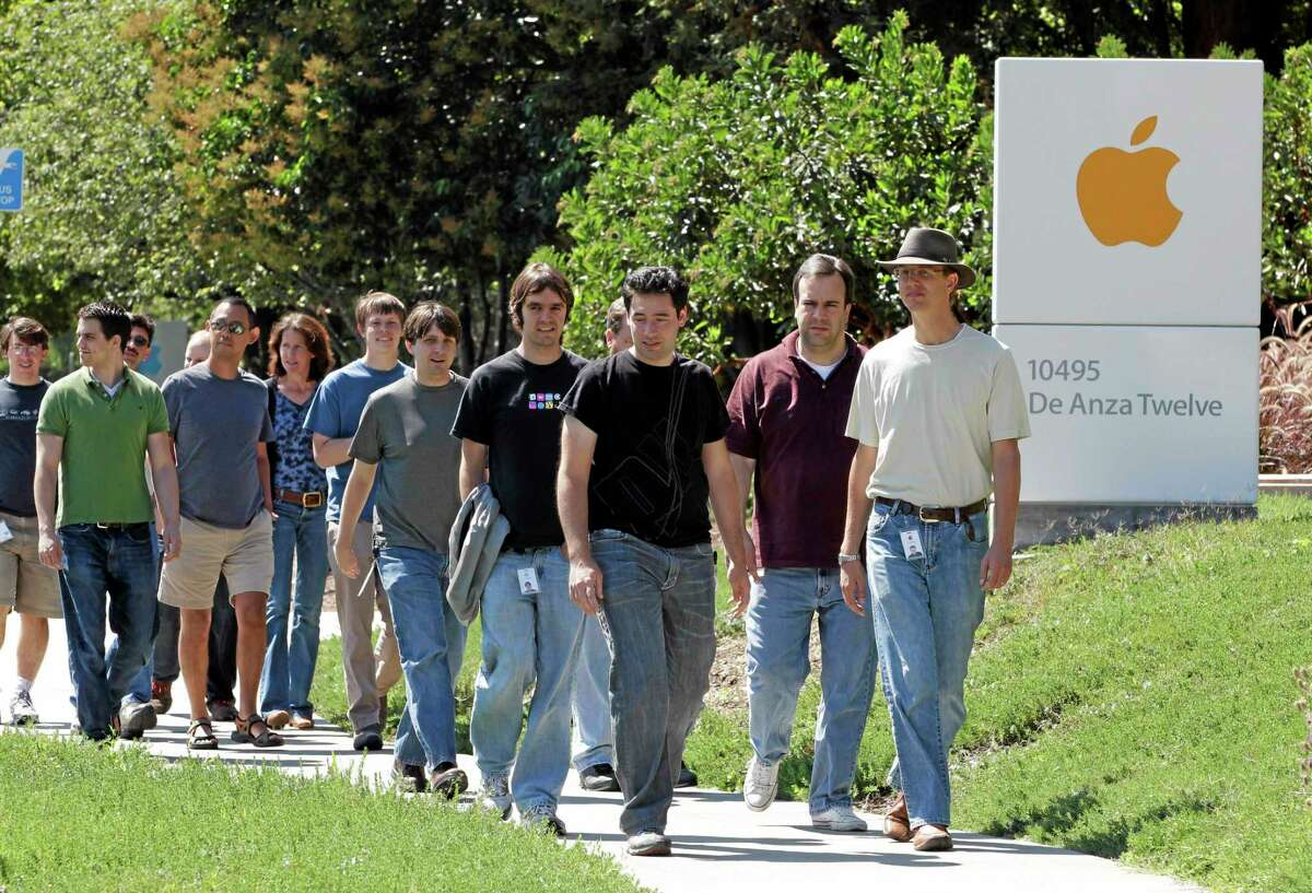 In this Aug. 25, 2011, photo, Apple employees walk between buildings at Apple headquarters in Cupertino, California.