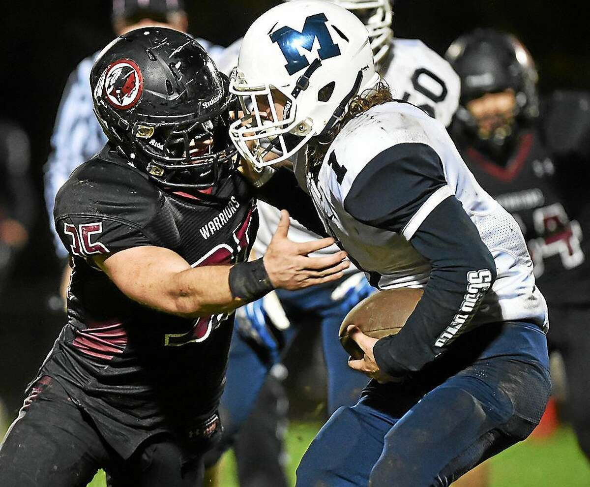 Valley Regional/Old Lyme senior linebacker Justin Cheverier stops Morgan's Joe Lee in the Warriors' 6-0 win. Cheverier holds the state record for most career tackles.