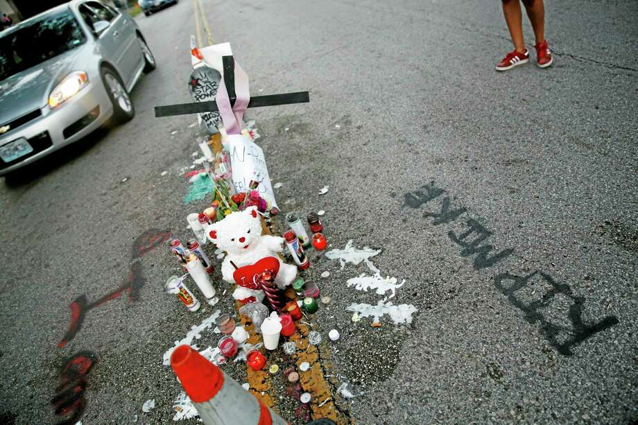 A makeshift memorial sits in the middle of the street where 18-year-old Michael Brown was shot and killed by police Monday, Aug. 11, 2014, in Ferguson, Mo. The FBI has opened an investigation into the fatal shooting of an unarmed black teenager on Saturday whose death stirred unrest in a St. Louis suburb. (AP Photo/Jeff Roberson) Photo: AP / AP