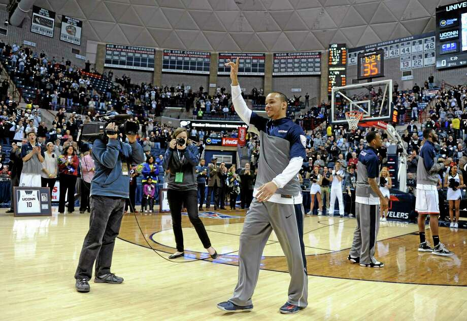 Shabazz Napier waves to the Gampel Pavilion crowd as the UConn seniors are recognized prior to the 19th-ranked Huskies' 69-63 win over Rutgers on Wednesday night in Storrs. Photo: Fred Beckham — The Associated Press  / FR153656 AP