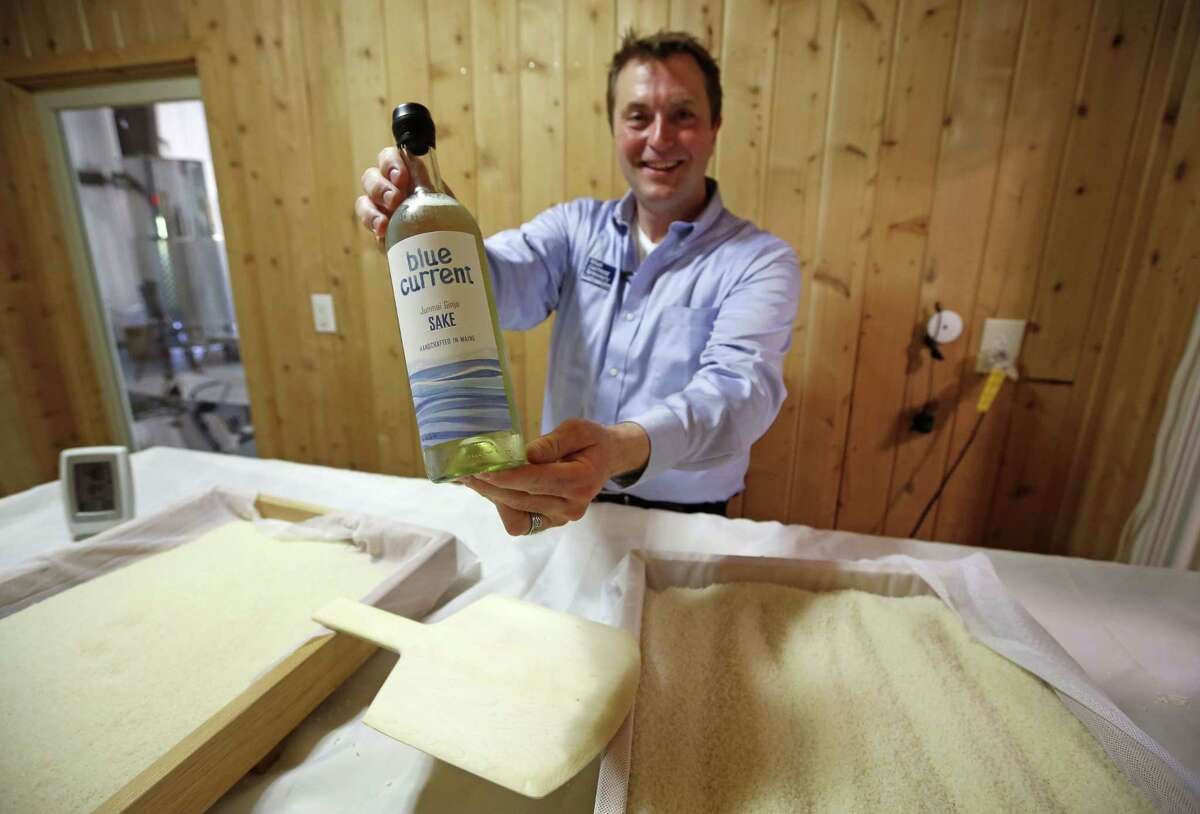 """Dan Ford, founder of the Blue Current Brewery, poses with a bottle of sake at the brewery in Kittery, Maine. Steamed rice is inoculated in a sauna-like koji room for two days as part of the six-week brewing process to make """"rice wine."""""""