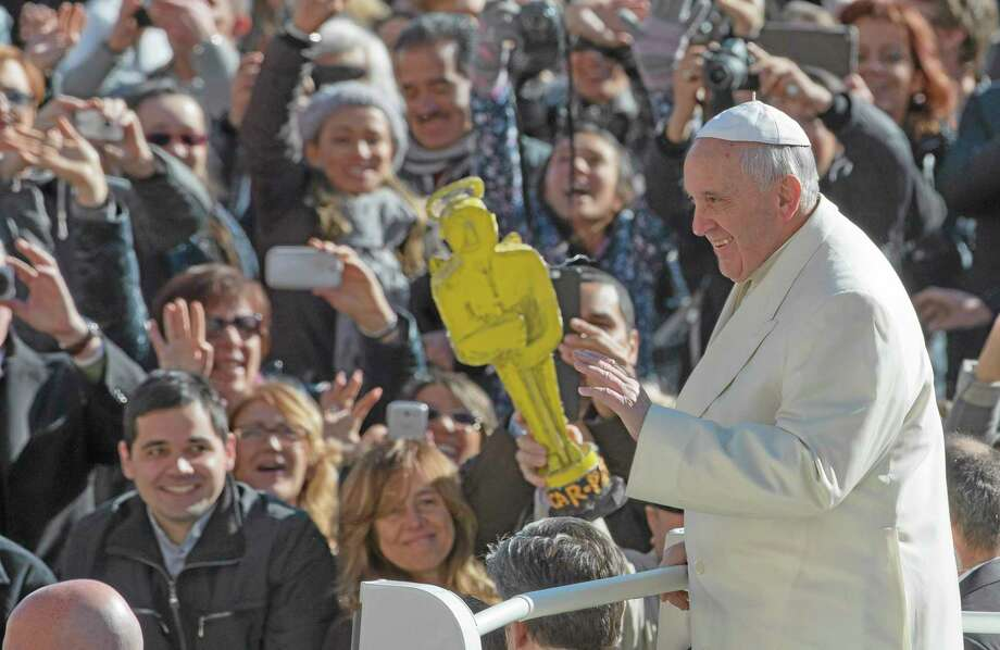 "A person holds a mock Oscar statue as Pope Francis tours St. Peter's Square at the Vatican prior to the start of his weekly general audience, Wednesday, March 5, 2014. The pontiff  says he finds the hype that is increasingly surrounding him ""offensive."" In an interview with Italian daily Corriere della Sera, Francis said he doesn't appreciate the myth-making that has seen him depicted as a ""Superpope"" who sneaks out at night to feed the poor. On Wednesday, a new Italian weekly hit newsstands ó a gossip magazine devoted entirely to the pope. Francis said: ""The pope is a man who laughs, cries, sleeps calmly and has friends like everyone else. A normal person."" (AP Photo/Alessandra Tarantino) Photo: AP / AP"