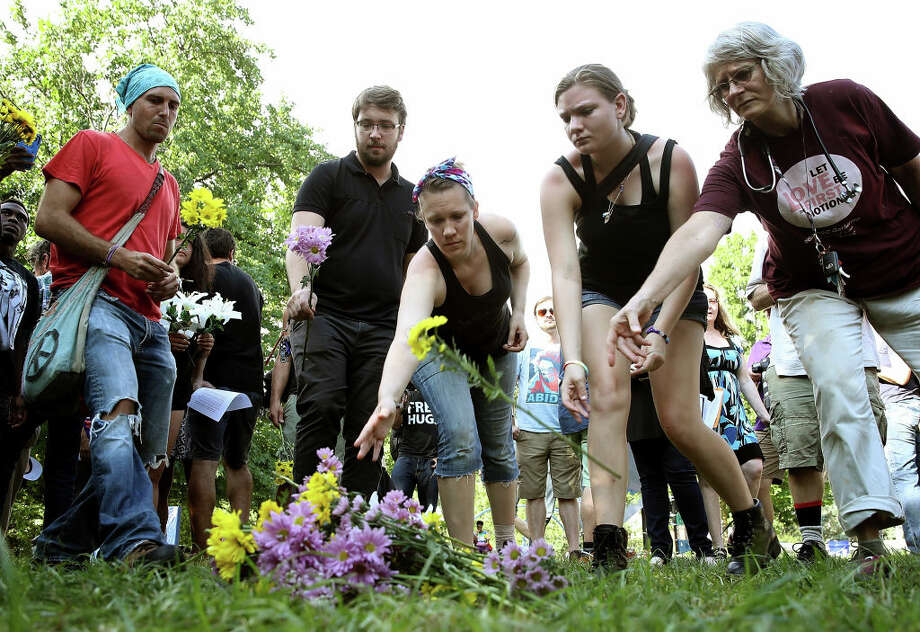 CHARLOTTESVILLE, VA - AUGUST 12:  People place flowers at a makeshift memorial during a vigil for those who were injured and died when a car plowed into a crowd of anti-facist counter-demonstrators marching near a downtown shopping area August 12, 2017 in Charlottesville, Virginia. The car allegedly plowed through a crowed, and at least one person has died from the incident, following the shutdown of the 'Unite the Right' rally by police after white nationalists, neo-Nazis and members of the 'alt-right' and counter-protesters clashed near Lee Park, where a statue of Confederate General Robert E. Lee is slated to be removed.  (Photo by Win McNamee/Getty Images) Photo: Win McNamee/Getty Images