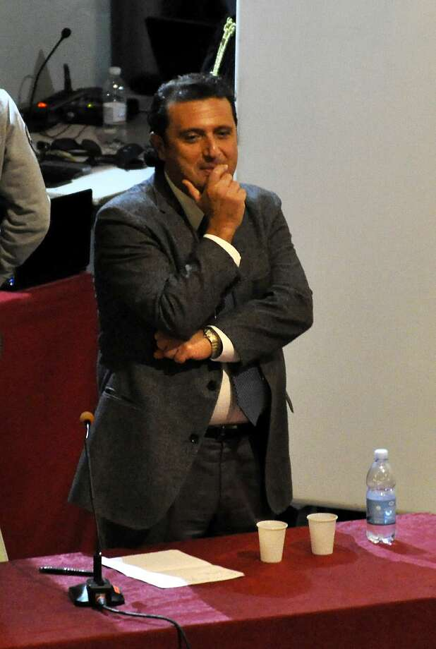 Francesco Schettino stands at the Grosseto court, Italy, Tuesday, Dec. 2, 2014. The captain of the Costa Concordia cruise ship offered his first court testimony Tuesday about the 2012 shipwreck off an Italian island that killed 32 people, sitting hunched behind a table on a theater's stage while prosecutors questioned him from the first row. While Francesco Schettino has long said he looked forward to his day in court to vindicate himself, he was granted a request not to have his image, and only his voice, broadcast from the theater that has served as a courtroom due to the widespread interest in the case. Schettino is being tried alone on charges of manslaughter, causing a shipwreck. (AP Photo/Giacomo Aprili) Photo: AP / AP