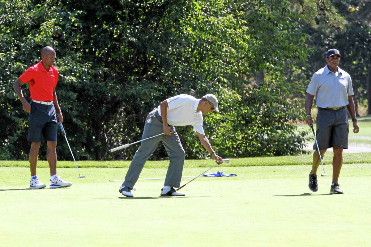 President Barack Obama, center, golfs with NBA player Ray Allen, left, and former NFL player Ahmad Rashad, at Farm Neck Golf Club in Oak Bluffs, Mass., Saturday, Aug. 9, 2014, on the first day of his vacation on the island of Martha's Vineyard. President Obama on Saturday fled Washington for his familiar spot on Martha's Vineyard for a two-week summer vacation, which comes as the U.S. is engaged in airstrikes against Islamic militant targets in Iraq. (AP Photo/Jacquelyn Martin)