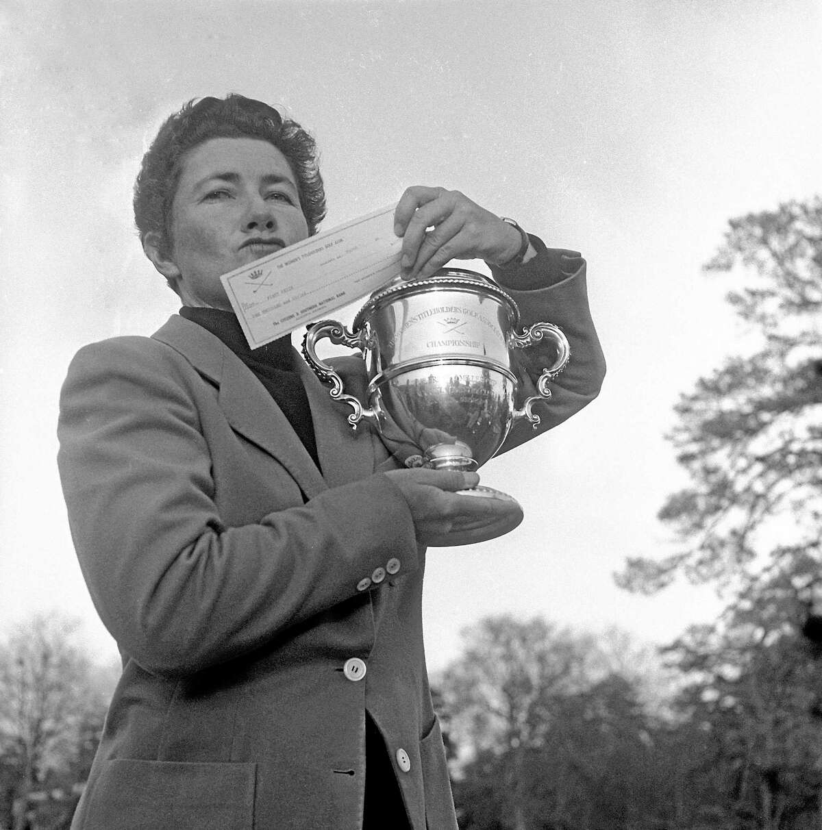 Louise Suggs holds up the winner's cup and a check for $1,000 after winning the Women's Titleholders championship in 1959 in Augusta, Ga.
