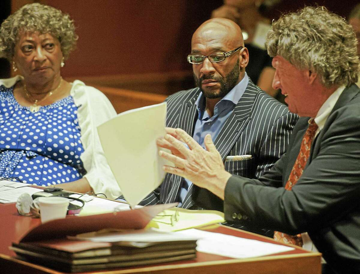 Irving Fryar, center, and his mother, Allene McGhee, left, sit in court July 21 at the Burlington County Courthouse in Mount Holly, N.J., and listen to Fryar's attorney, Michael Gilberti, as they wait for jury selection to begin.
