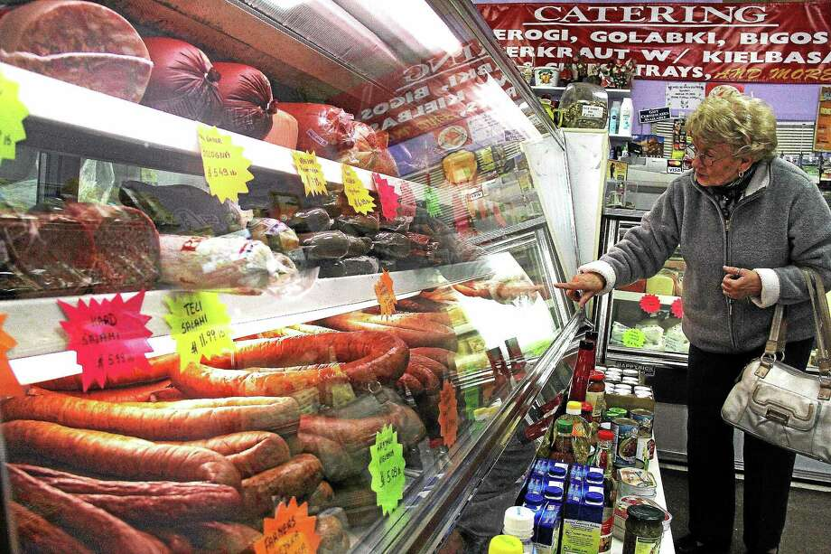 A shopper at Fil's Polish Deli in Cromwell orders some kielbasa for an Easter dinner she will cook for a dozen people this weekend. Photo: Kathleen Schassler — Middletown Press  / Kathleen Schassler All Rights