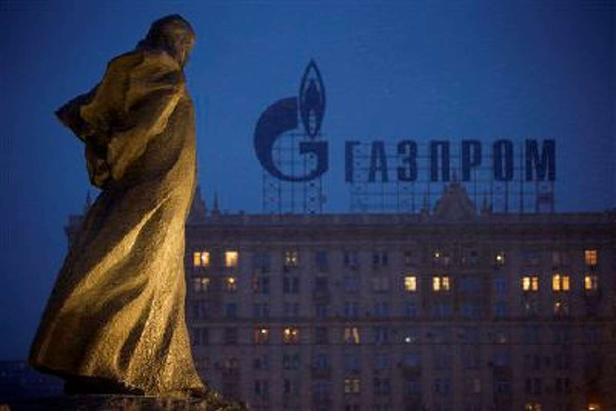 A monument to Ukrainian poet and writer Taras Shevchenko is silhouetted against an apartment building with a sign advertising Russia's natural gas giant Gazprom, in Moscow, Russia, Tuesday, March 4, 2014. Russia's state-controlled natural gas giant Gazprom said Tuesday it will cancel a price discount on gas it sells to Ukraine. Russia had offered the discount in December as part of Russian help for Ukraine. Gazprom also said Ukraine owes it $1.5 billion. (AP Photo/Alexander Zemlianichenko)