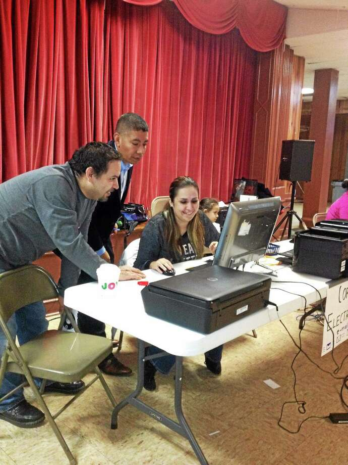 Eric Amenta and Cecilio Cuapio help Daniela Mungia apply for a DMV written test at a session set up at St. Rose of Lima Church New Haven. Photo: MARY O'LEARY — NEW HAVEN REGISTER