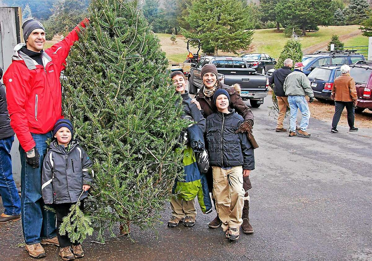 Robb and Nancy Barnum take a moment to pose with their three sons, Devan, 11, Kyle, 9, and Ryan, 5, after purchasing an evergreen tree last year at Hale Hill Farm Charity Day in Portland. This year, the charity event will be held from noon to 5 p.m. Dec. 13. Proceeds benefit Operation Fuel, a statewide energy assistance program.