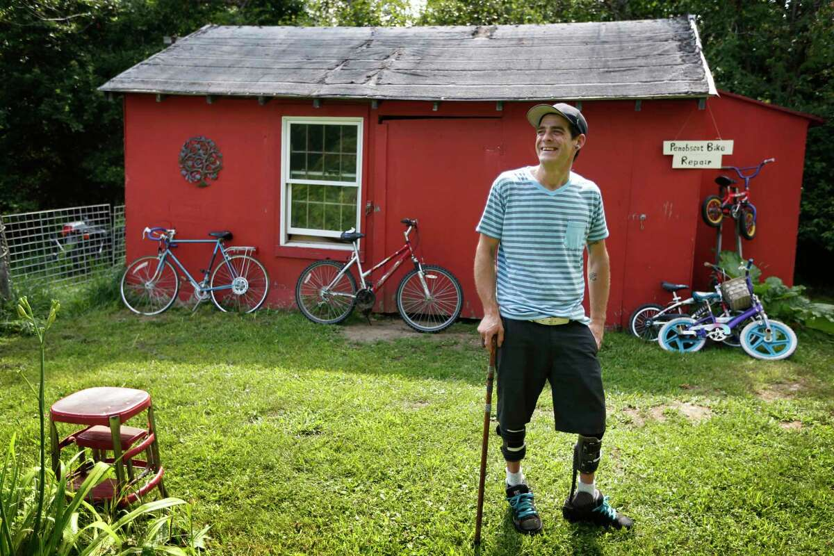 In Thursday, July 30, 2015, photo Ryan Kinsella poses outside his bicycle repair business in Penobscot, Maine. Kinsella broke his back in a rock climbing accident in 2002. The accident left him with partially paralyzed legs. He is recovering from a long battle with hepatitis C, which he contracted by sharing IV drug needles.