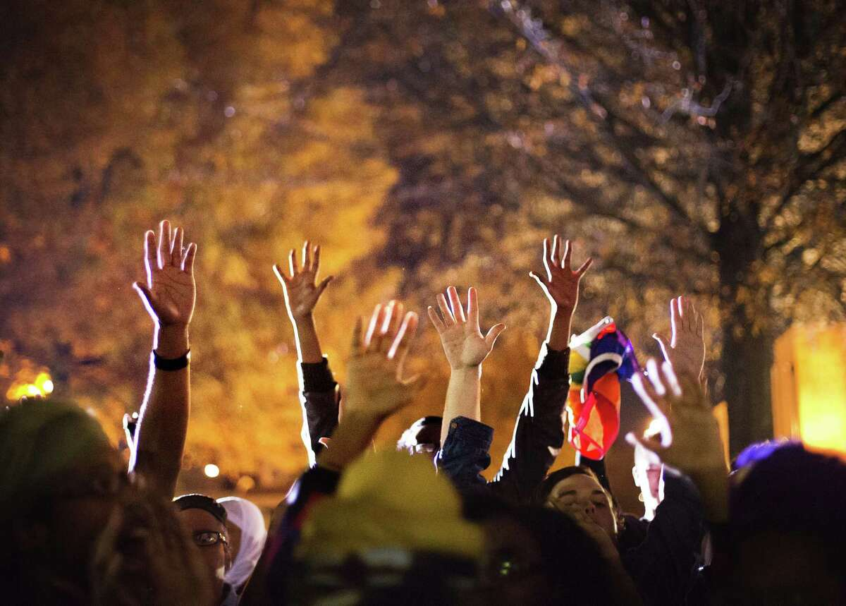 """Protesters hold up their hands while chanting """"hands up don't shoot"""" outside Ebenezer Baptist Church, the church where The Rev. Martin Luther King Jr. preached, as U.S. Attorney General Eric Holder speaks inside to members of the community during an interfaith service Monday."""