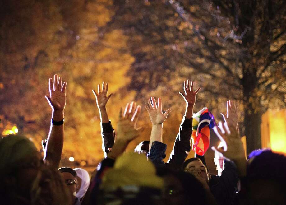 """Protesters hold up their hands while chanting """"hands up don't shoot"""" outside Ebenezer Baptist Church, the church where The Rev. Martin Luther King Jr. preached, as U.S. Attorney General Eric Holder speaks inside to members of the community during an interfaith service Monday. Photo: AP Photo  / AP"""