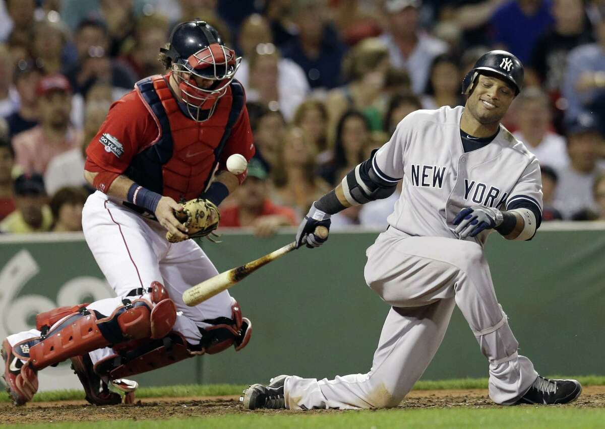 Boston Red Sox catcher Jarrod Saltalamacchia keeps the ball in front as New York Yankees' Robinson Cano swings for a strike in the fifth inning of a baseball game at Fenway Park in Boston on July 6, 2012.