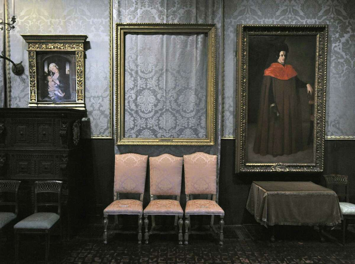 """In this March 11, 2010, file photo, the empty frame, center, from which thieves cut Rembrandt's """"Storm on the Sea of Galilee"""" remains on display at the Isabella Stewart Gardner Museum in Boston. More than a dozen works were stolen from the museum on March 18, 1990. On Thursday, Aug. 6, 2015, the U.S. Attorney's Office released a surveillance video showing an automobile outside the rear entrance and an unauthorized visitor entering the museum 24 hours before the robbery."""