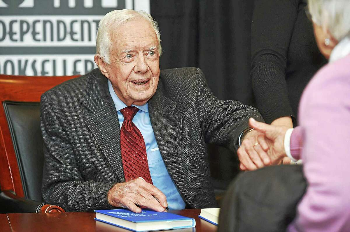 "Jimmy Carter, 39th president of the United States, shakes hands before signing a copy of his book, ""A Call to Action: Women, Religion, Violence and Power,"" at the New Haven Lawn Club Tuesday in New Haven."