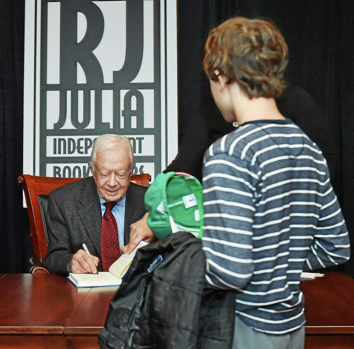 "Jimmy Carter, 39th president of the United States, signs a copy of his book, ""A Call to Action: Women, Religion, Violence and Power,"" at the New Haven Lawn Club Tuesday in New Haven."
