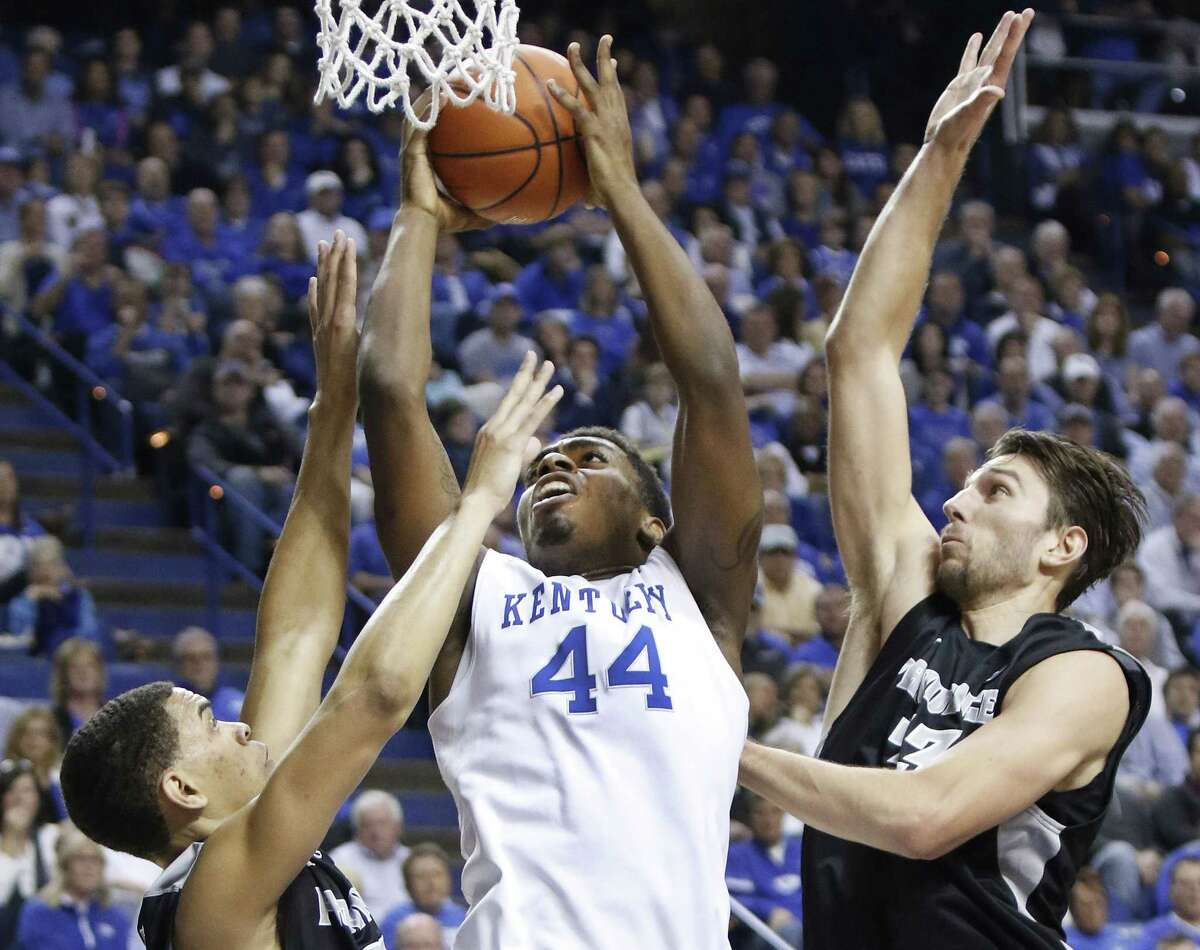 Kentucky's Dakari Johnson (44) shoots between Providence defenders Tyler Harris, left, and Carson Desrosiers, right, during the first half Sunday.