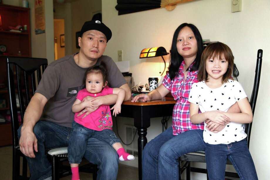 Korean adoptee Adam Crapser, left, poses with daughters, Christal, 1, Christina, 5, and his wife, Anh Nguyen, in the family's living room in Vancouver, Wash. on March 19, 2015. Crapser, whose adoptive parents neglected to make him a U.S. citizen, will face an immigration judge and could be separated from his family and deported to South Korea, a country he does not know. (AP Photo/Gosia Wozniacka) Photo: AP / AP