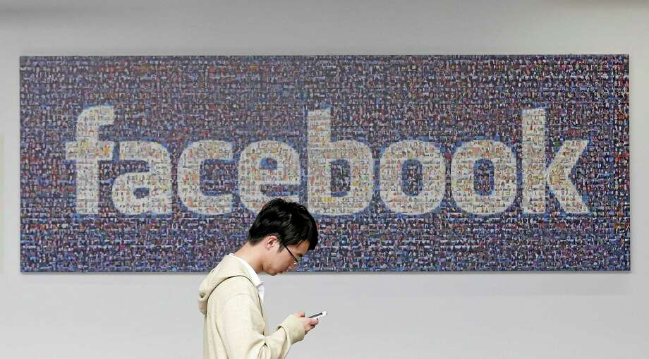 A man walks past a Facebook sign in an office on the Facebook campus in Menlo Park, California. Photo: Jeff Chiu — The Associated Press  / AP
