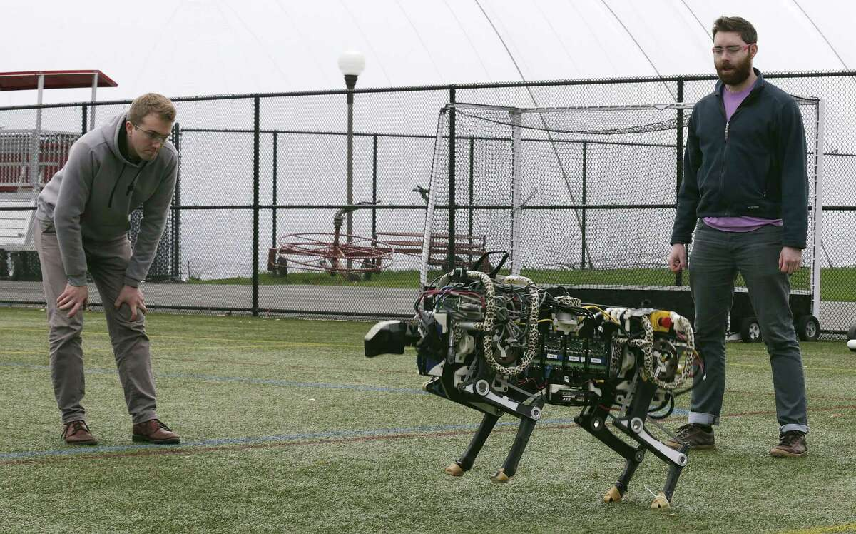 Researchers Randall Briggs, left, and Will Bosworth monitor a robotic cheetah during a test run on an athletic field Oct. 24 at the Massachusetts Institute of Technology in Cambridge, Mass. MIT scientists said the robot, modeled after the fastest land animal, may have real-world applications, including for prosthetic legs.