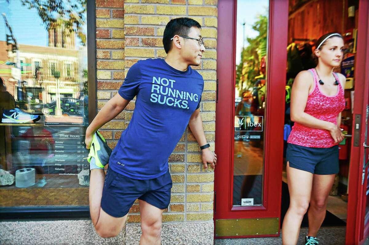 """New Haven resident Jian """"C.J."""" Cao stretches at Trailblazer on Elm Street Tuesday before going out for a run during the New Haven Road Race 20K training series."""