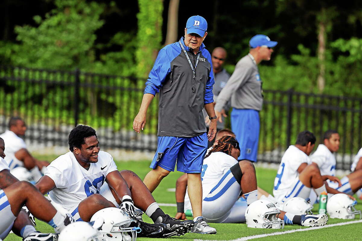 In this Aug. 5, 2013 photo, Duke coach David Cutcliffe chats with players as they stretch during an NCAA college football practice in Durham, N.C. A growing number of college coaches are watching the social media behavior of student athletes, including Cutcliffe.
