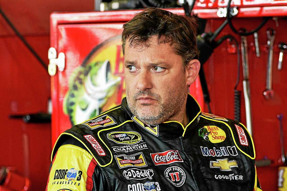 In this Aug. 8, 2014 photograph, Tony Stewart stands in the garage area after a practice session for Sunday's NASCAR Sprint Cup Series auto race at Watkins Glen International, in Watkins Glen N.Y.