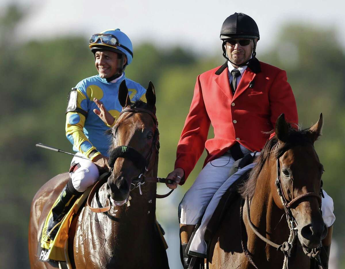 Jockey Victor Espinoza, on Triple Crown winner American Pharoah, waves after winning the Haskell Invitational on Sunday at Monmouth Park in Oceanport, N.J.