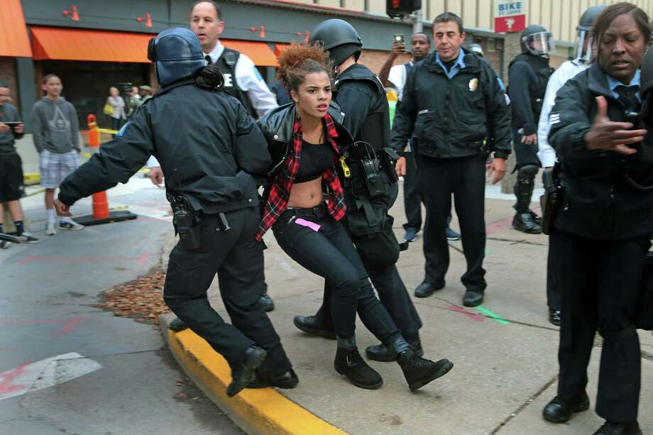 Police arrest a protester on Sunday at Kiener Plaza in St. Louis. Protesters and police clashed following an NFL football game between the St. Louis Rams and the Oakland Raiders as protests continued following a grand jury's decision not to indict a Ferguson police officer in the shooting death of Michael Brown. Photo: AP Photo  / The St. Louis Post-Dispatch