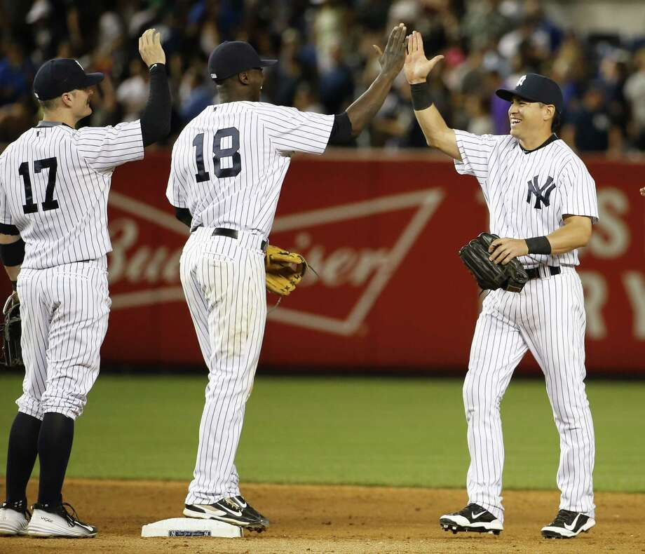 Yankees second baseman Brendan Ryan (17), and shortstop Didi Gregorius (18) congratulate Jacoby Ellsbury, right, after the Yankees 2-1 victory over the Red Sox on Thursday. Photo: Kathy Willens — The Associated Press  / AP