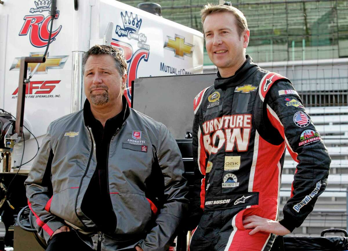 In this May 9, 2013 file photo, Andretti Autosport team owner Michael Andretti, left, and NASCAR driver Kurt Busch wait for the start of a testing session at the Indianapolis Motor Speedway. Busch and Andretti Autosport announced Tuesday that he will try to become the first driver in 10 years to run the Indianapolis 500 and the Coca-Cola 600 on the same day.