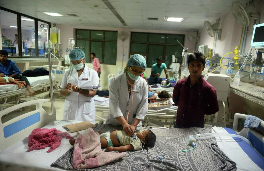 Indian medical staff attend to a child in the encephalitis ward at the Baba Raghav Das hospital in Gorakhpur, where dozens of children have died in the past three days. Photo: SANJAY KANOJIA / Sanjay Kanojia / AFP / Getty Images / AFP or licensors