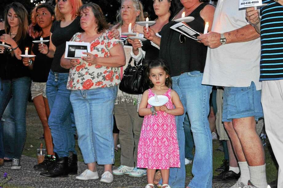 "After three weeks missing, family and friends of Nina Coe, 56, of Middletown say it's getting ""harder and harder every day"" to pray she'll be found safe and sound. Here, nearly 100 gather for a candlelight vigil on the South Green Aug. 5. Photo: Cassandra Day — The Middletown Press"