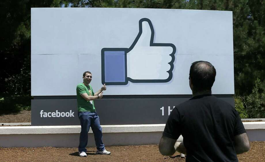 In this June 11, 2014, file photo, a man poses for photographs in front of the Facebook sign on the Facebook campus in Menlo Park, Calif. Photo: AP Photo/Jeff Chiu, File / AP