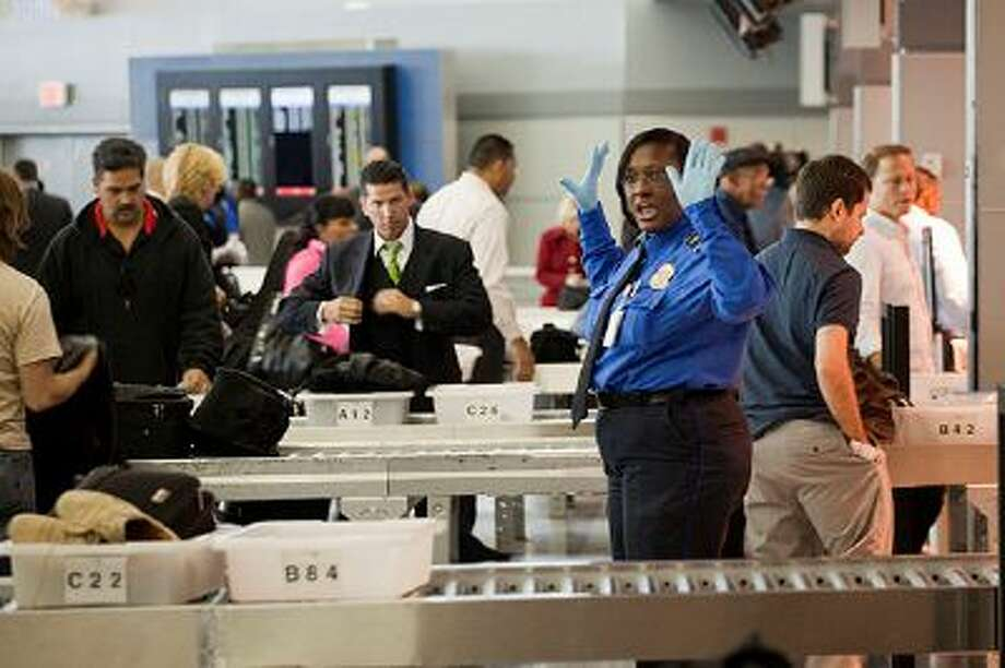NEW YORK - OCTOBER 22:  A TSA officer gives directions to passengers at John F. Kennedy International Airport's Terminal 8 passenger security checkpoint on October 22, 2010 in the Queens borough of New York City.  Earlier today at Terminal 8, the TSA introduced new backscatter X-ray full-body scanners that can see through clothing and will screen passengers for metallic and non-metallic threats including explosives.  (Photo by Michael Nagle/Getty Images) Photo: Getty Images / 2010 Getty Images
