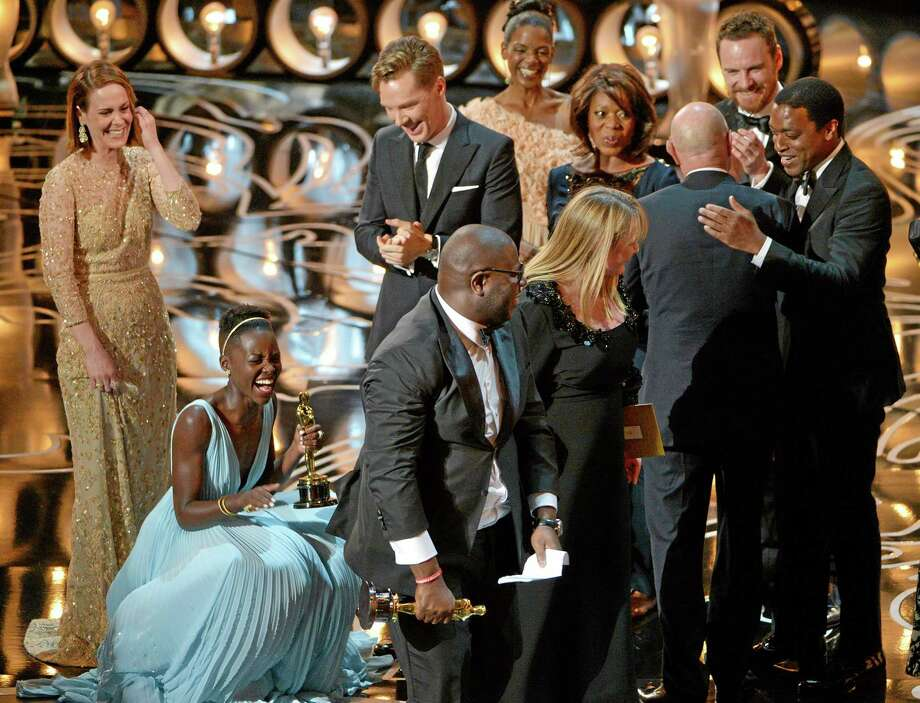 "Sarah Paulson, left, stands near as Lupita Nyong'o, second from left, celebrates after accepting the award for best picture of the year for ""12 Years a Slave"" during the Oscars at the Dolby Theatre on Sunday, March 2, 2014, in Los Angeles.  (Photo by John Shearer/Invision/AP) Photo: John Shearer/Invision/AP / Invision"