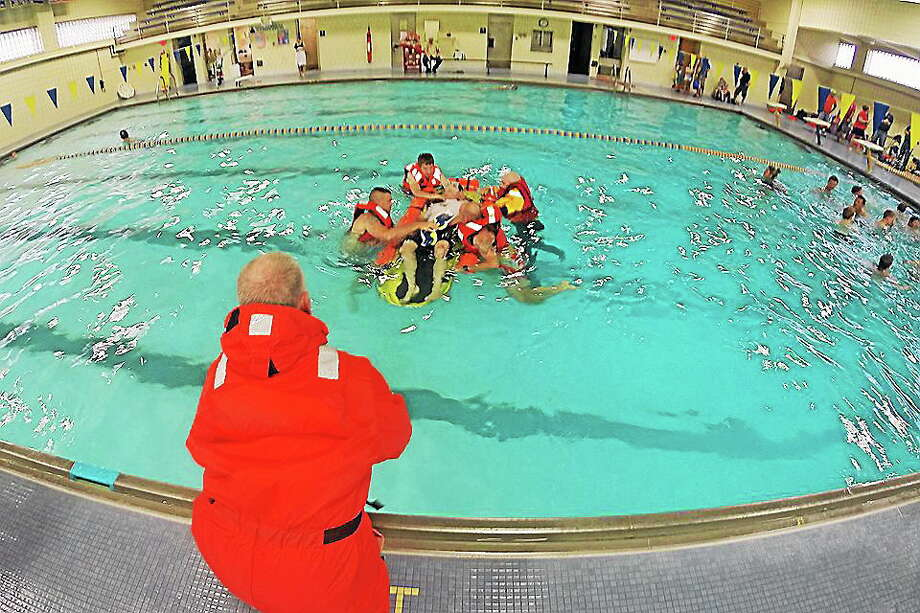 Haddam Volunteer Fire Co. members took part in water rescue exercise July 21 at the Haddam-Killingworth High School pool. Photo: Jesse Drake - Special To The Press