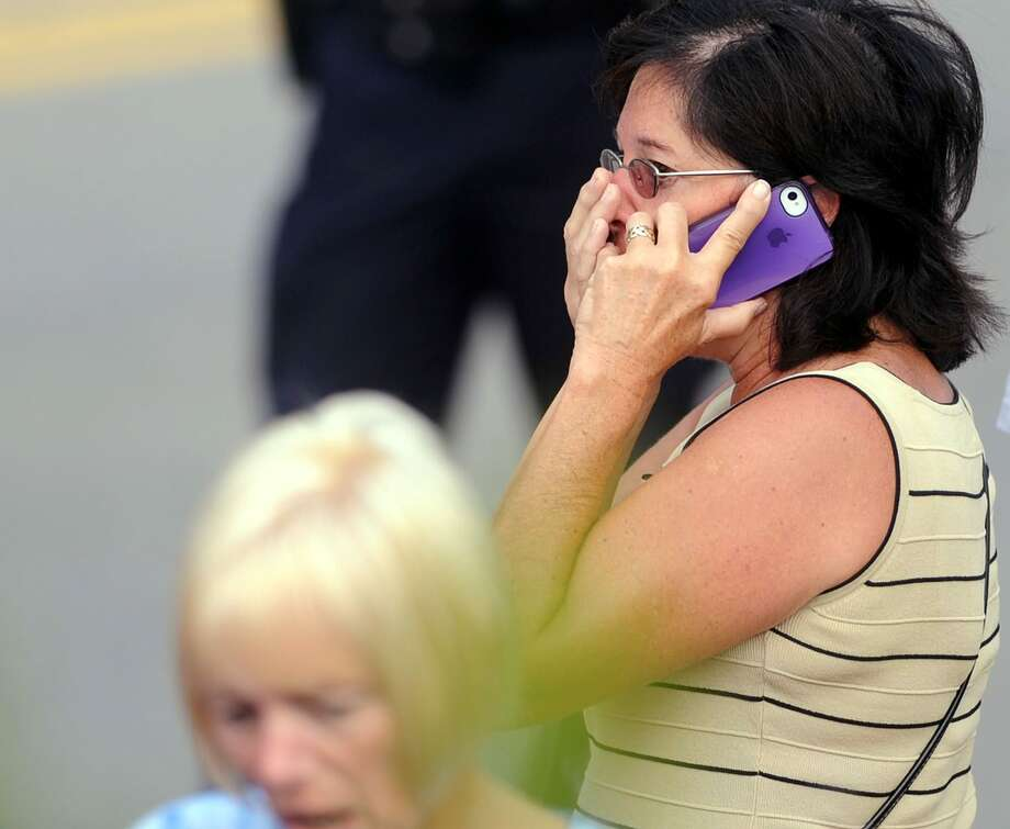 A woman who didn't want to be named, cries while on her phone as the statue of former Penn State football coach Joe Paterno is removed at Beaver Stadium in State College, Pa., on Sunday, July 22, 2012. The university announced earlier Sunday that it was taking down the monument in the wake of an investigative report that found the late coach and three other top Penn State administrators concealed sex abuse claims against retired assistant coach Jerry Sandusky. (AP Photo/Centre Daily Times, Christopher Weddle) MANDATORY CREDIT; MAGS OUT Photo: File Photo / Centre Daily Times